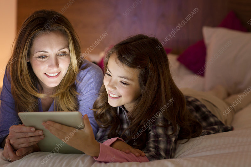 Mother and daughter using tablet on bed