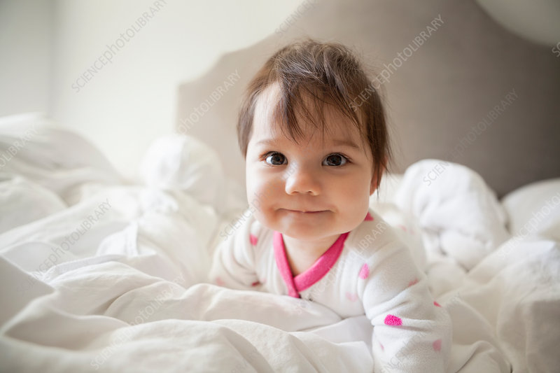 Baby girl crawling in bedsheets