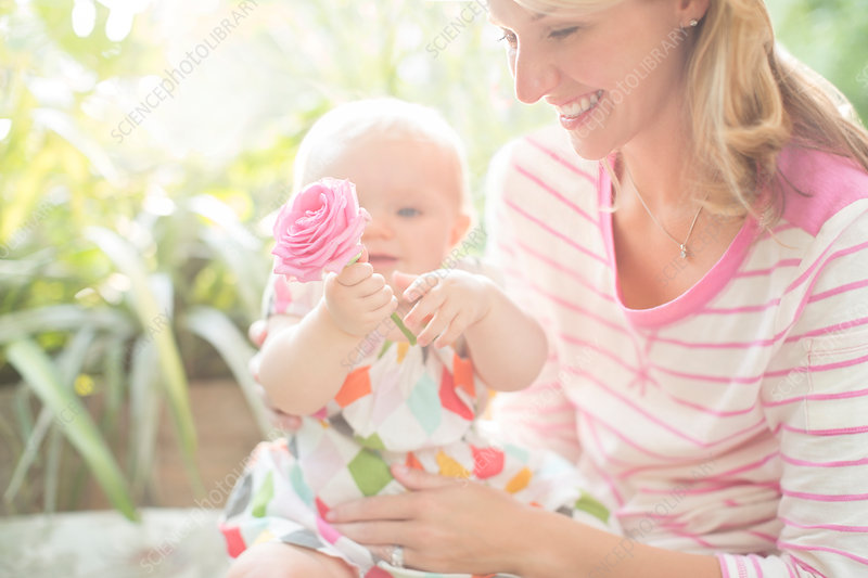 Mother and baby girl playing with flower