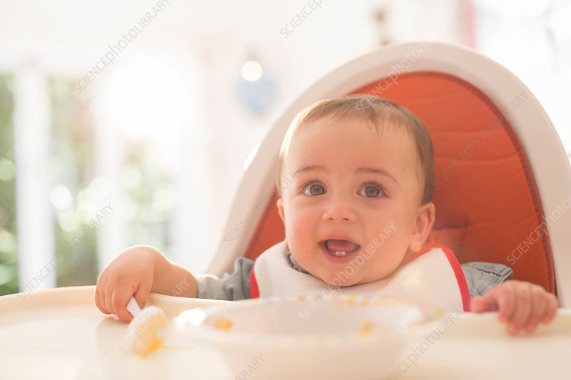Baby boy eating in high chair
