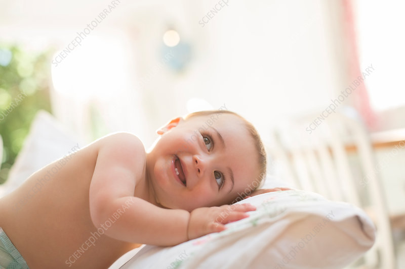 Baby boy leaning on pillow