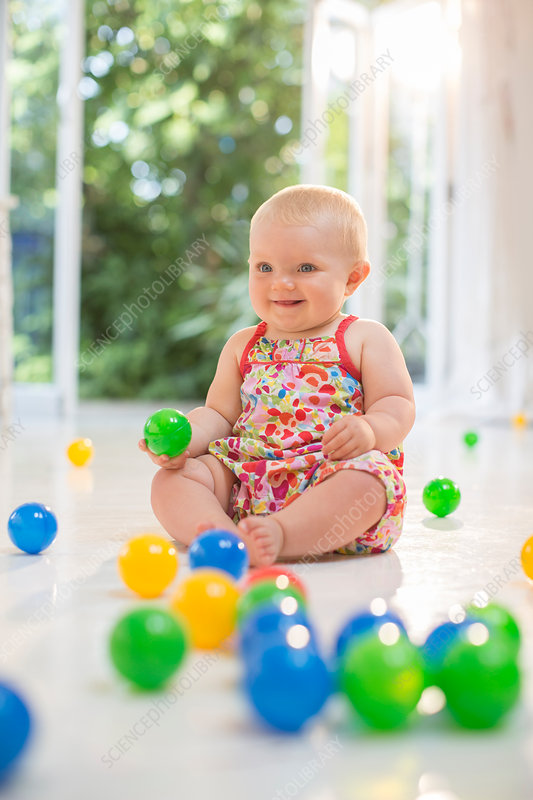 Baby girl playing with toys on floor