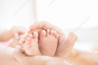 Father cradling baby boy's feet