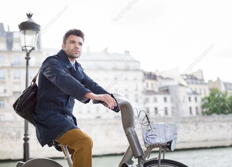 Businessman riding bicycle in Paris