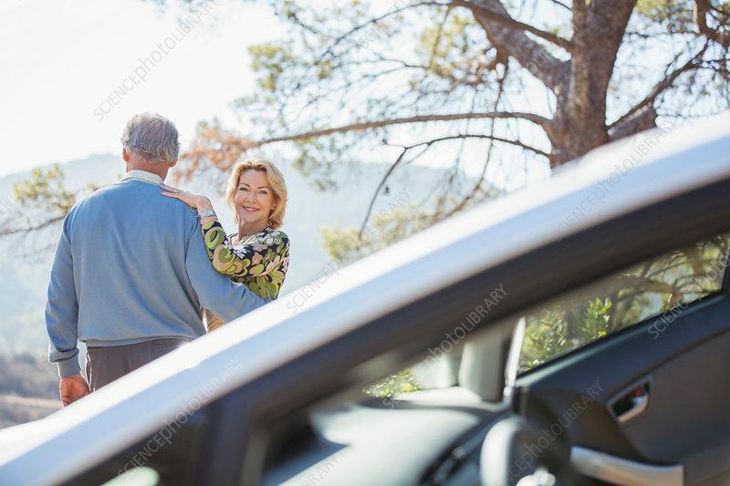 Senior couple hugging at roadside