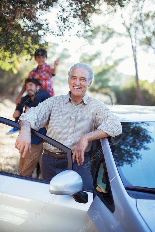 Senior man leaning against car