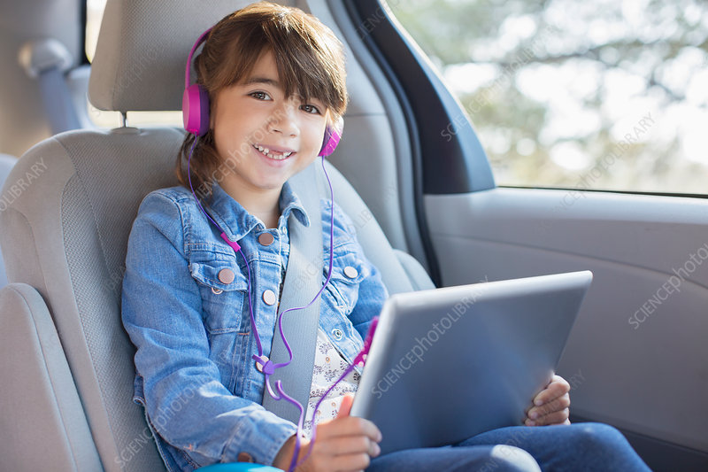 Smiling girl with headphones using tablet