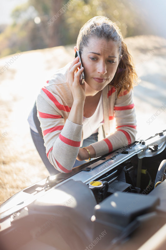 Frustrated woman looking at car engine