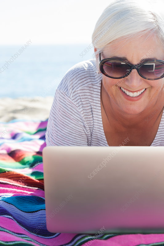 Happy woman using laptop on beach