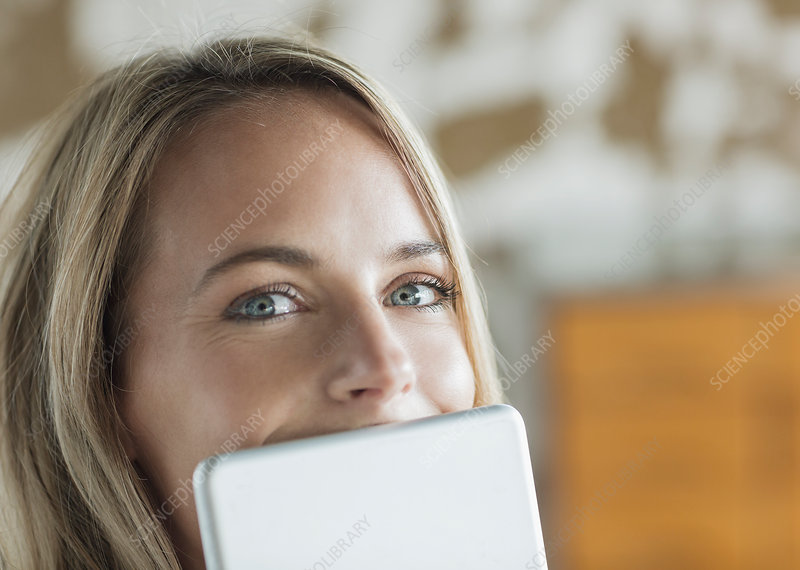 Close up portrait of woman behind tablet