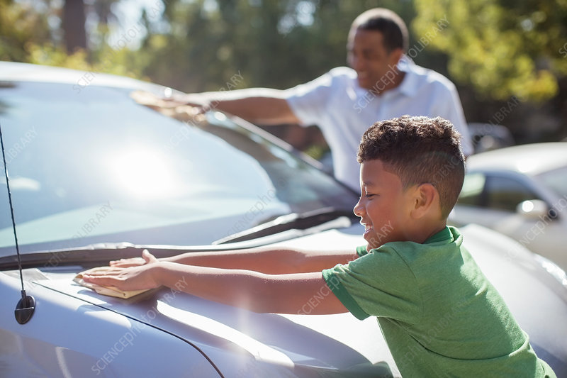 Grandfather and grandson wiping car