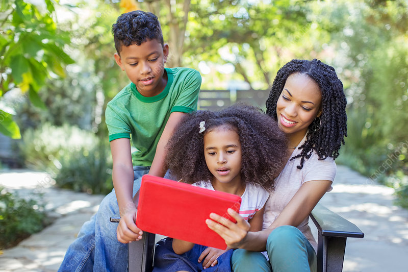 Mother and children using digital tablet
