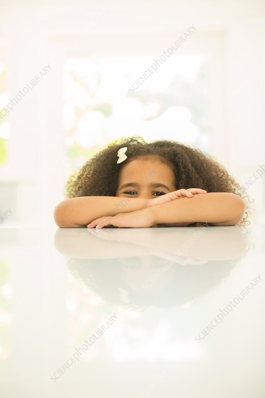 Portrait of girl leaning on table