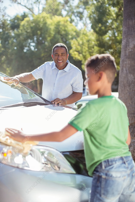 Grandfather and grandson washing car