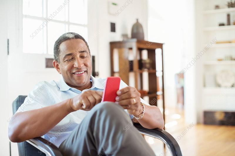 Senior man text messaging in living room
