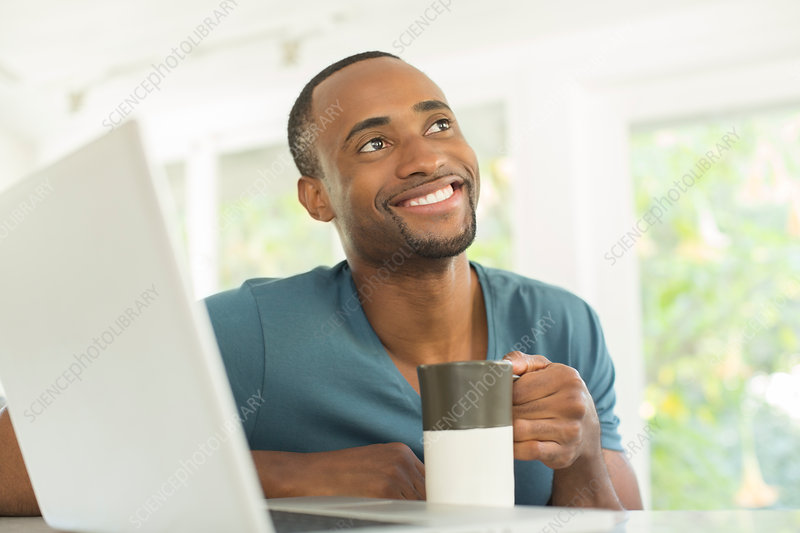 Happy man drinking coffee at laptop
