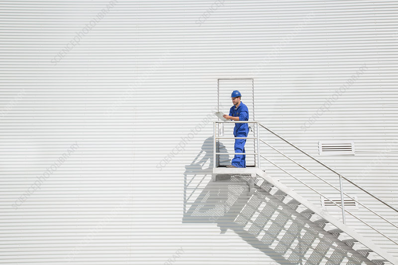 Worker on stairs along building