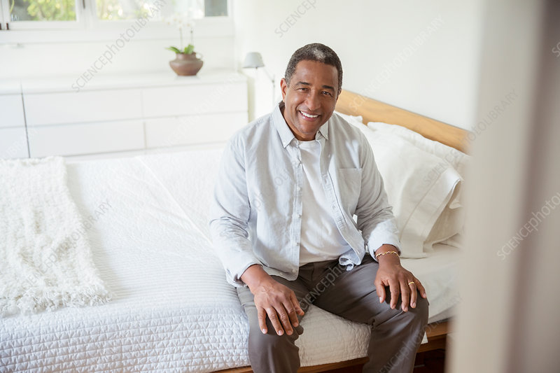 Smiling senior man sitting on bed