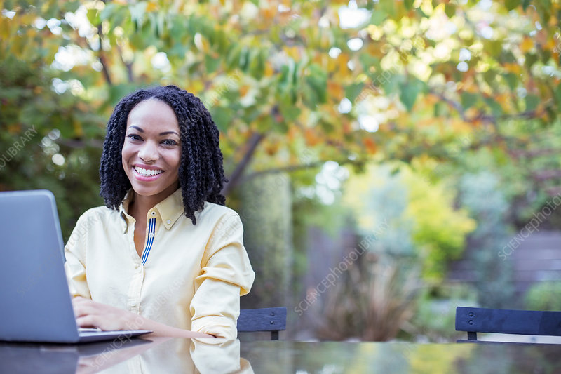 Smiling woman using laptop at patio table