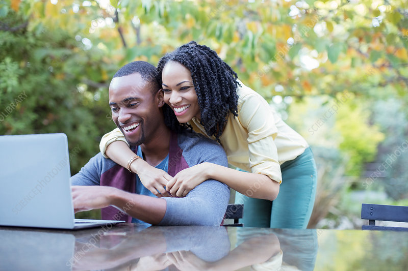 Happy couple using laptop at patio table