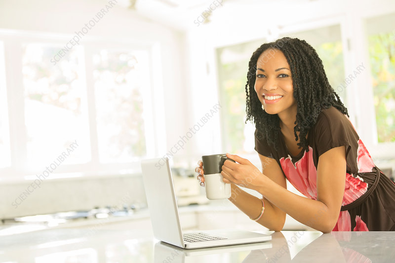Smiling woman drinking coffee at laptop