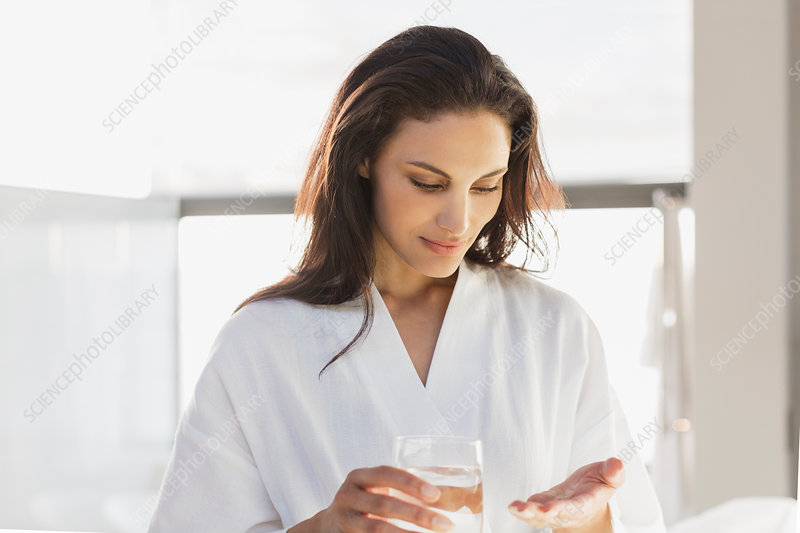Woman in bathrobe taking medication