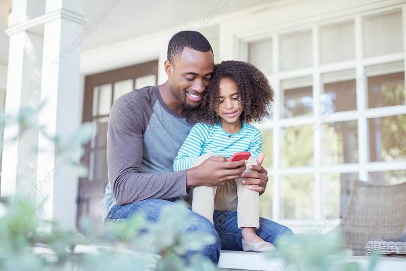 Father and daughter using cell phone