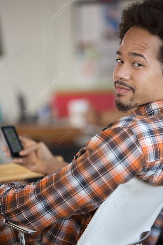 Portrait of confident man text messaging