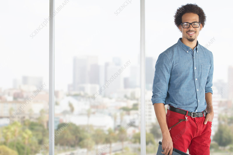 Businessman at window overlooking city