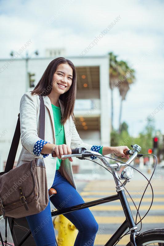 Businesswoman on bicycle on urban street