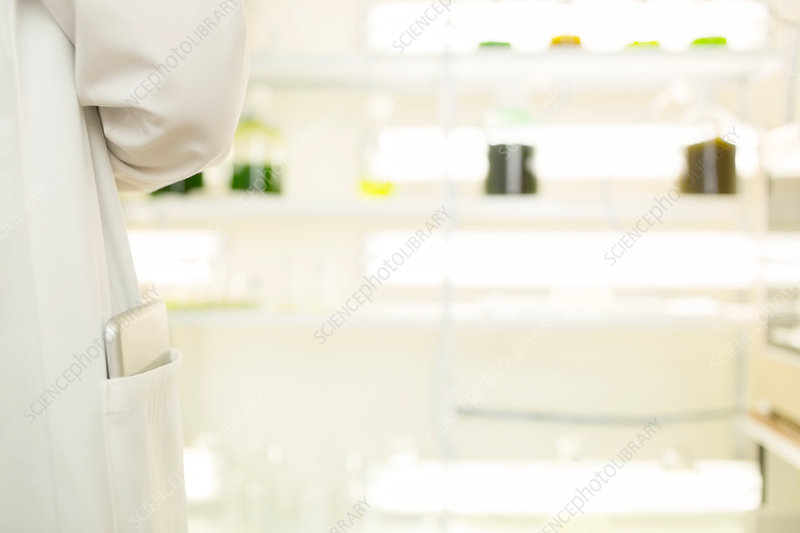 Tablet in scientist's lab coat pocket