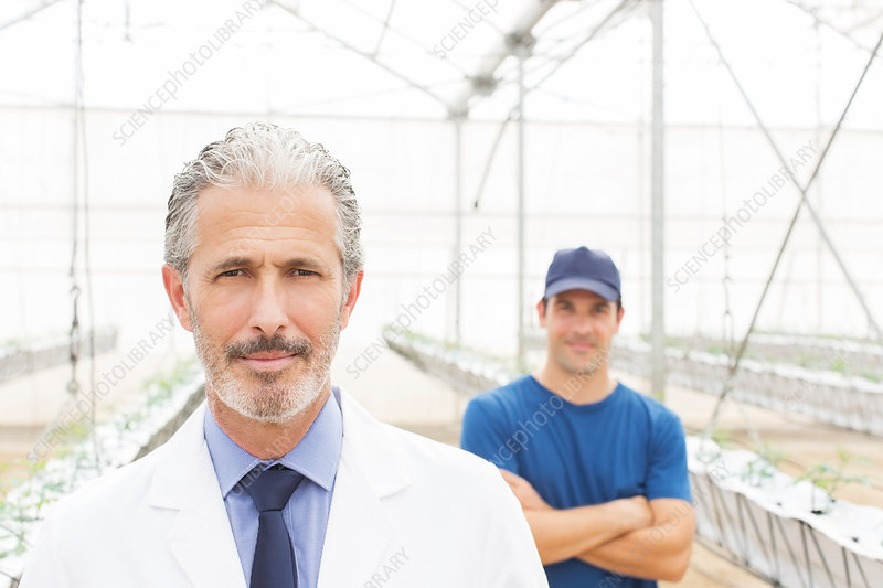 Scientist and worker in greenhouse