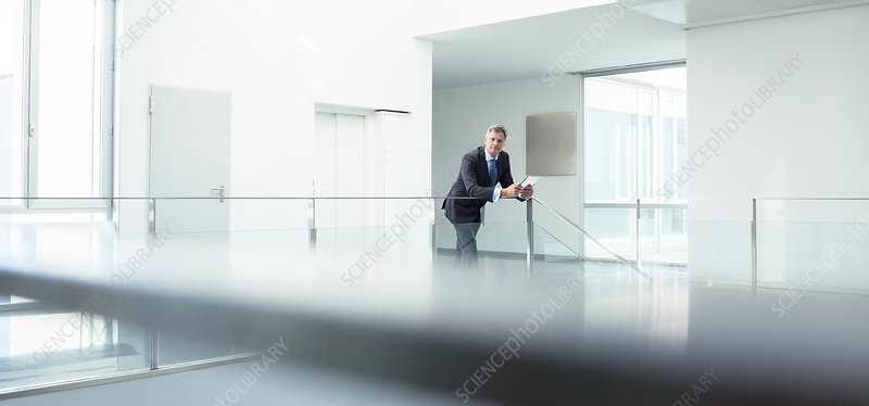 Businessman standing at railing in office