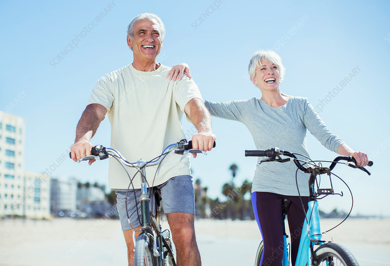 Senior couple with bicycles on beach