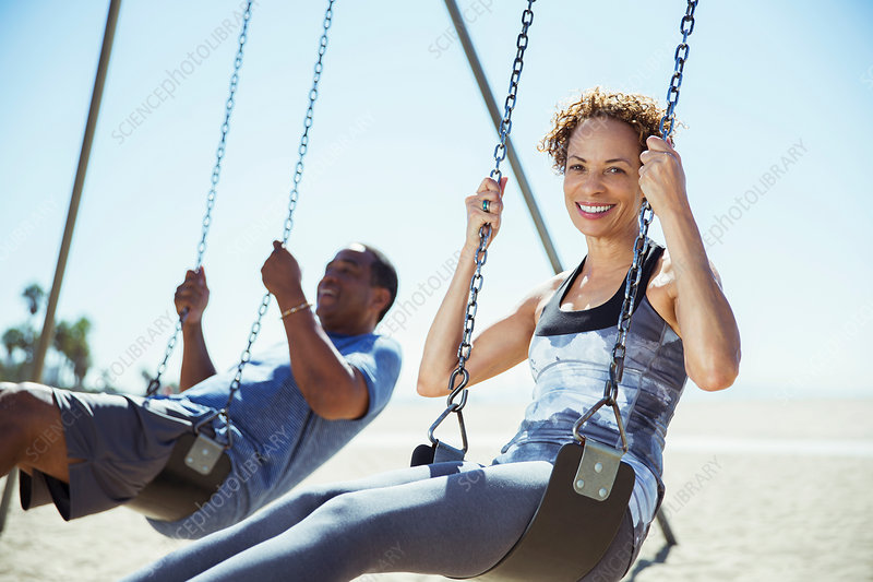 Couple on swings at beach