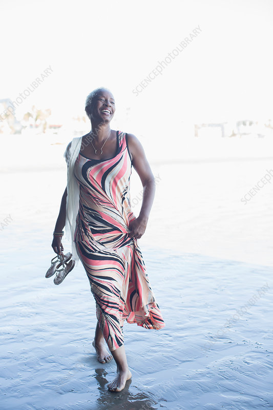 Happy woman in dress walking barefoot