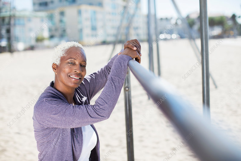 Woman leaning on bar at beach playground