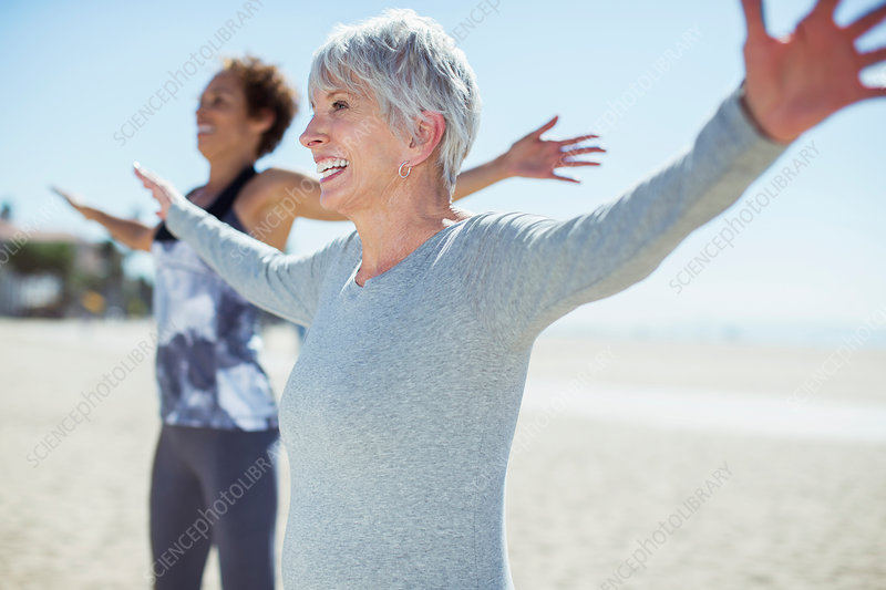 Senior women stretching arms on beach