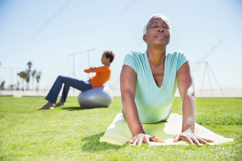 Women practicing yoga in sunny park