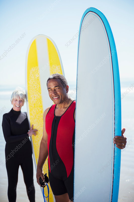 Portrait of senior couple with surfboards