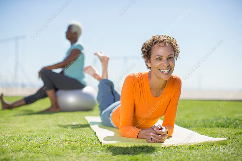 Woman on yoga mat in park