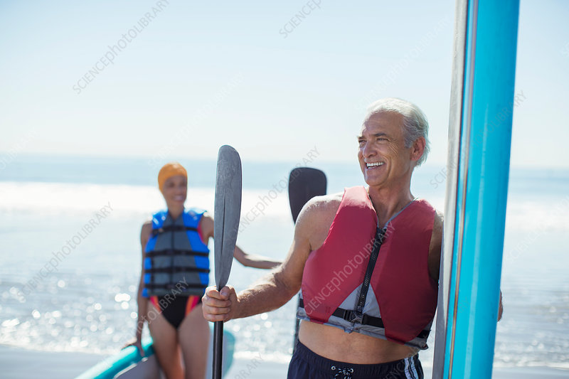 Senior couple with paddleboards on beach