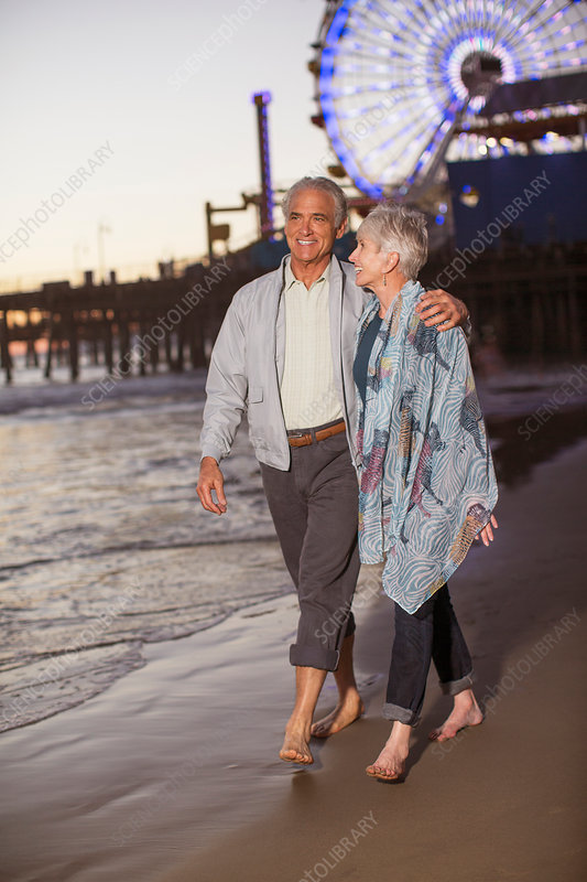 Senior couple walking on beach at sunset