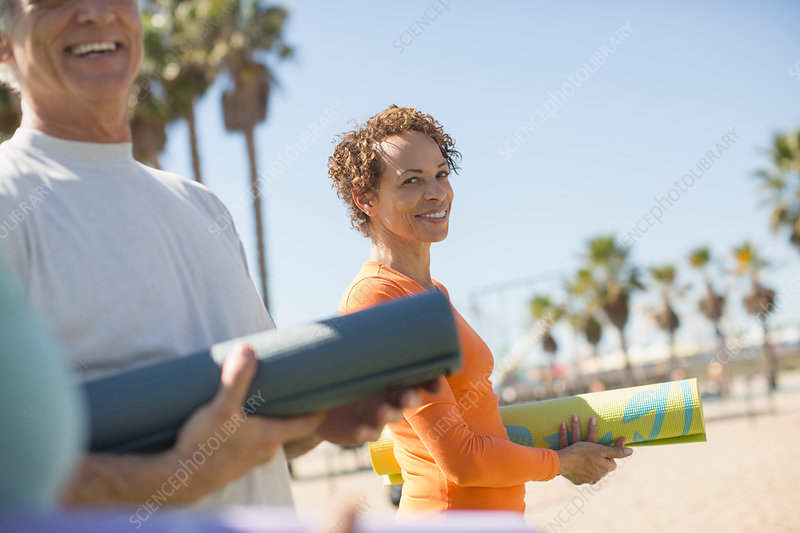 Woman with yoga mat at beach