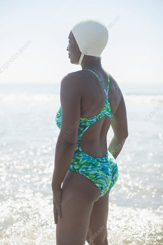 Pensive woman in bathing suit and cap