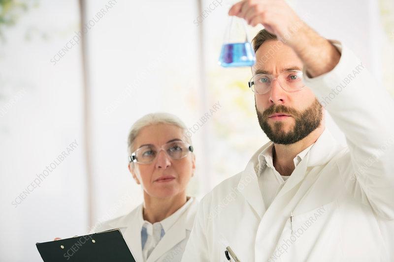 Scientists examining liquid
