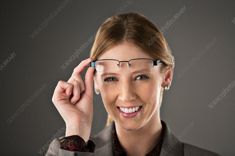 Businesswoman raising eyeglasses