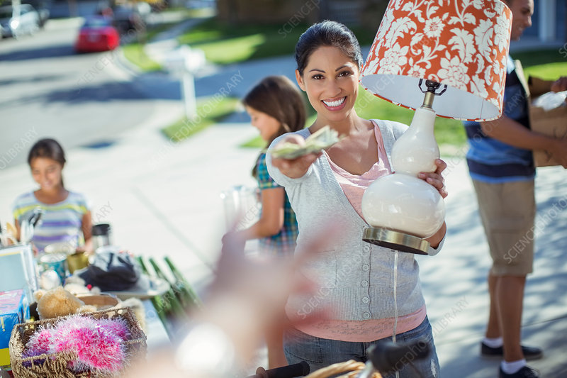 Woman paying for lamp at yard sale