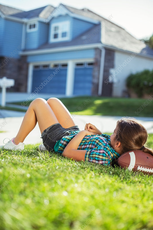 Girl laying on football in grass