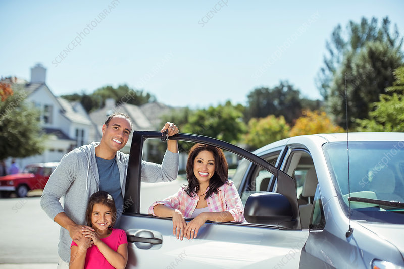 Portrait of family at car in driveway